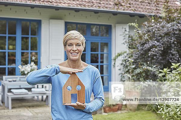 Portrait of smiling woman standing in front of her home holding house model