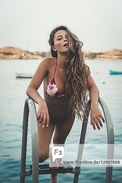 Teenage girl in sexy bikini  standing on ladder to the sea