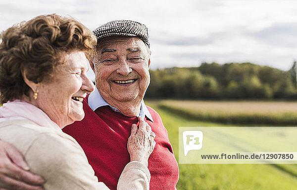 Happy senior couple embracing in rural landscape