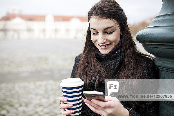 Portrait of young woman with coffee to go leaning against lamp pole looking at cell phone