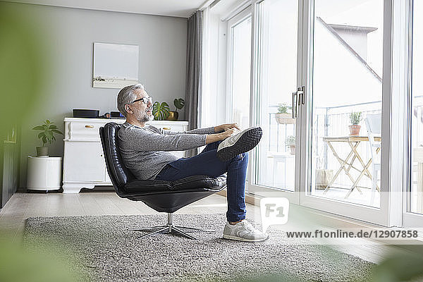 Mature man relaxing on leather chair in his living room looking out of window