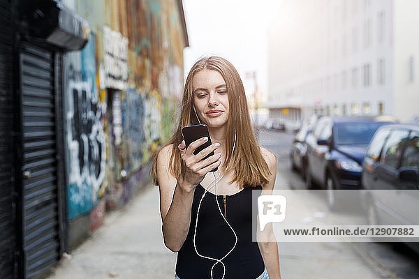 Young woman walking in street  listening music  using smartphone