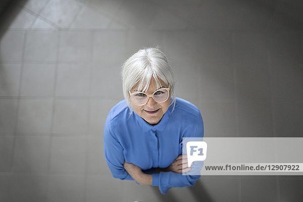 Smiling senior businesswoman looking up on office hallway