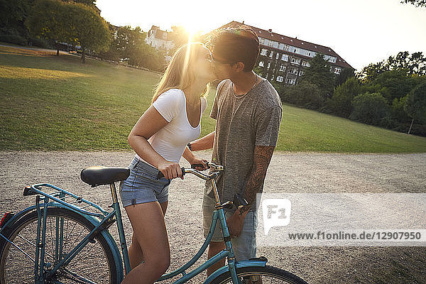 Young woman with bicycle  kissing her boyfriend in park