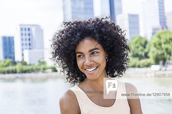 Germany  Frankfurt  portrait of smiling young woman with curly hair in front of Main River