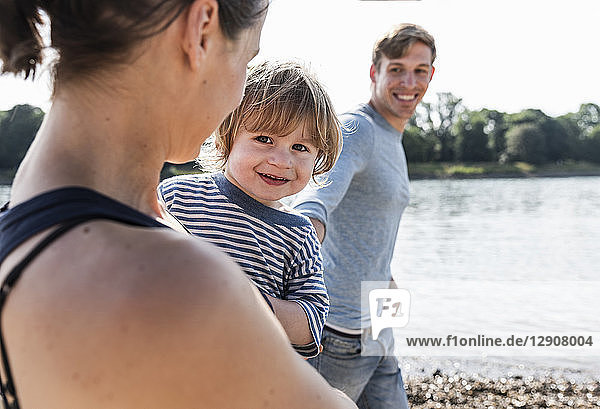 Happy family walking at the river on a beautiful summer day