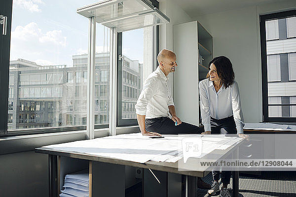 Two architects working in office  discussing blueprints