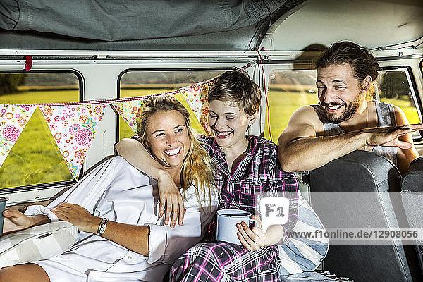Happy friends inside a van enjoying coffee