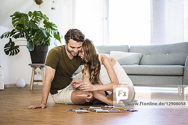 Happy affectionate couple sitting at home looking at photographies on the floor