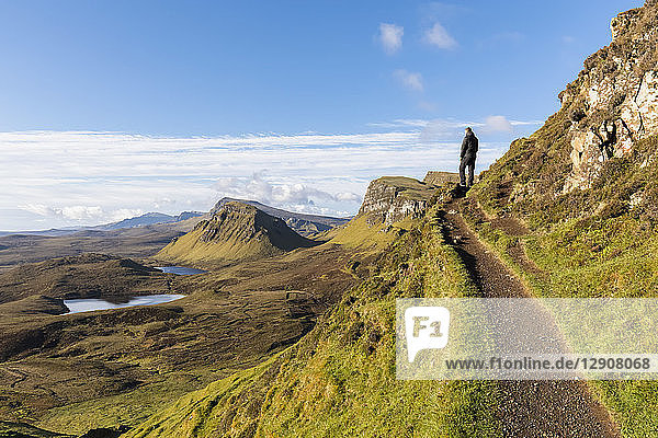 UK  Scotland  Inner Hebrides  Isle of Skye  Trotternish  hiking trail at Quiraing  Loch Cleat  hiker looking at view