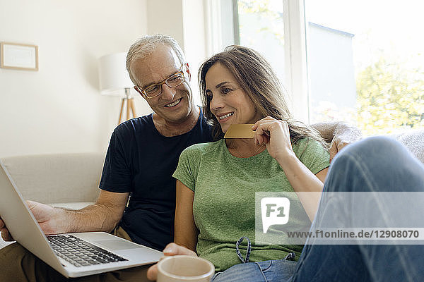 Smiling mature couple sitting on couch at home shopping online with laptop