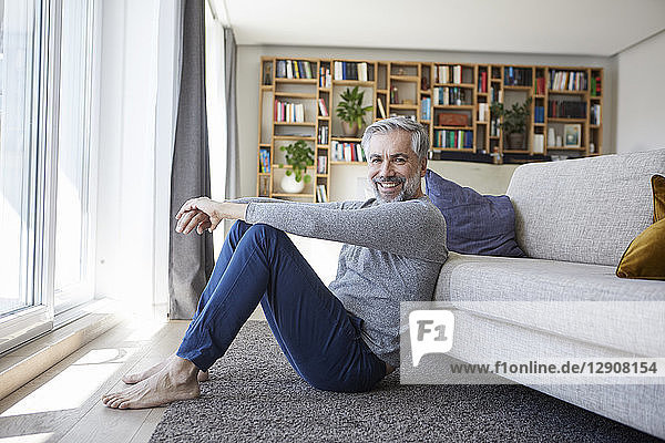 Portrait of happy mature man sitting on floor of his living room