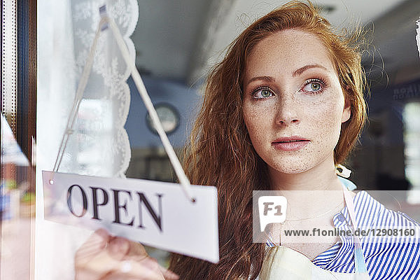 Young woman opening a shop