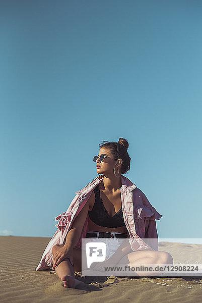 Teenage girl sitting on beach dune against blue sky