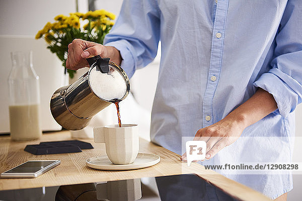 Young woman pouring coffee in cup