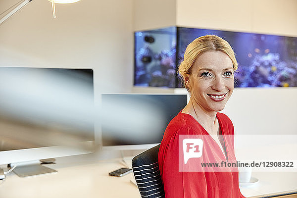 Portrait of smiling young woman sitting at desk in office