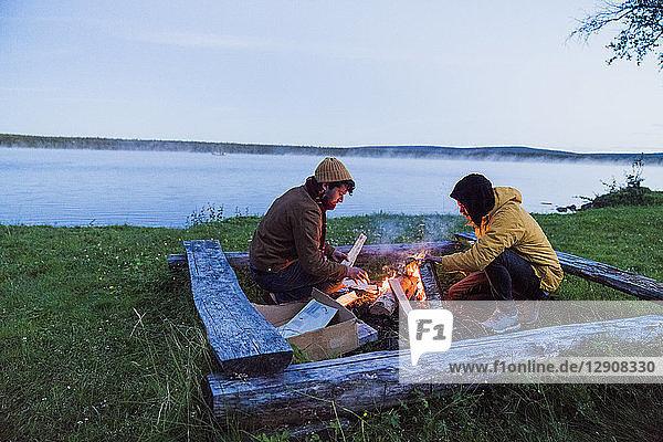 Sweden  Lapland  Two friends preparing a bonfire at the lakeshore
