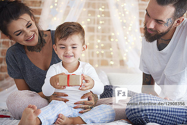 Happy family celebrating Christmas in bed
