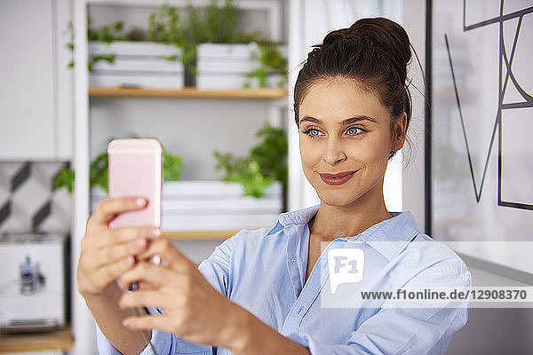Young woman at home in kitchen  taking selfie