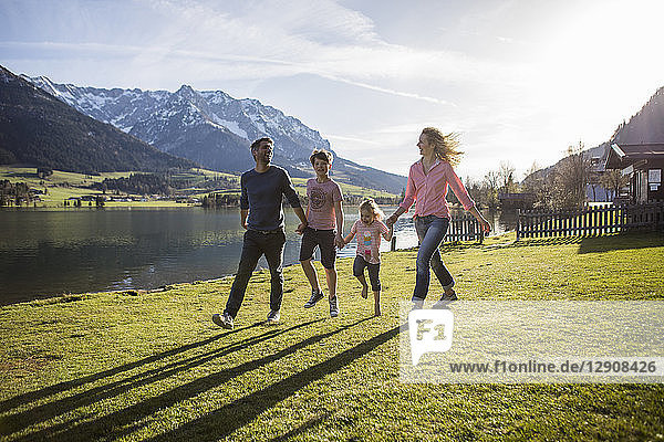 Austria  Tyrol  Walchsee  happy family walking at the lakeside