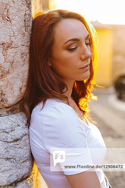 Portrait of redheaded woman leaning against wall at sunset