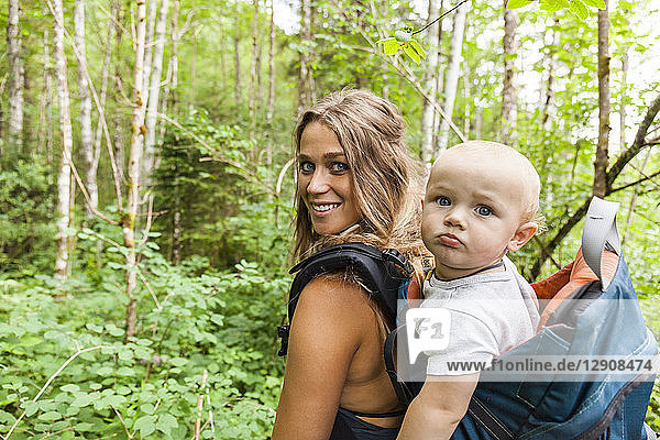 Portrait of smiling mother hiking in the woods with baby boy in backpack