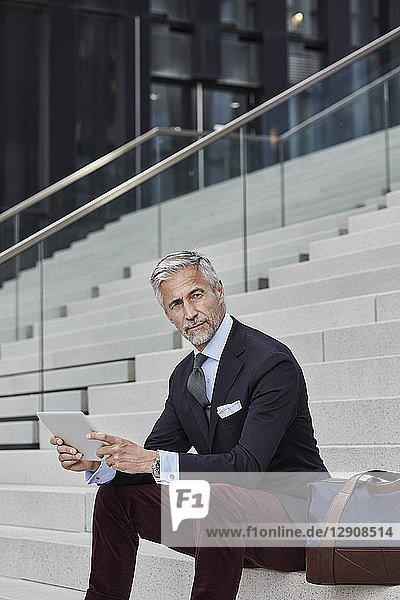 Portrait of fashionable businessman with travelling bag and tablet sitting on stairs Portrait of fashionable businessman with travelling bag and tablet sitting on stairs