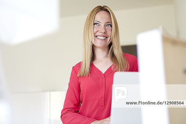 Laughing woman in red blouse  using laptop