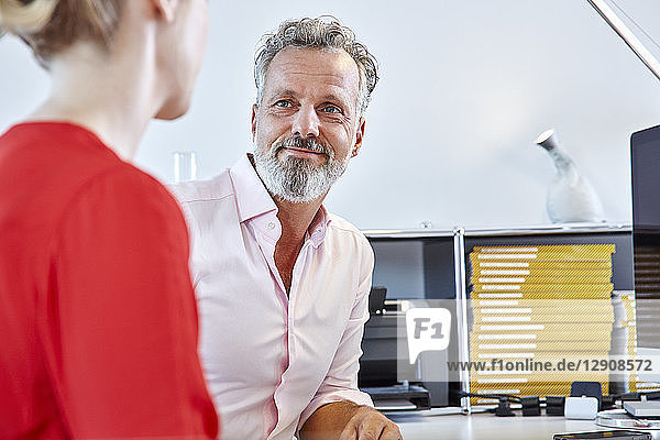 Mature man looking at female colleague at desk in office