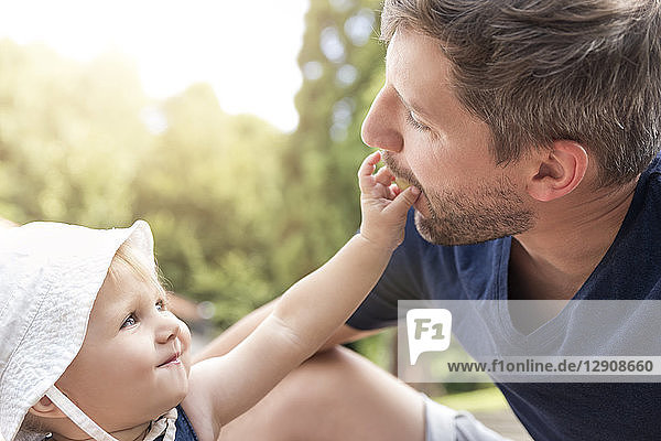 Little girl feeding father with a grape
