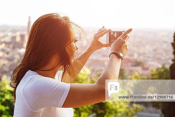 Italy  Verona  Italy  Verona  redheaded woman taking photo with smartphone by sunset