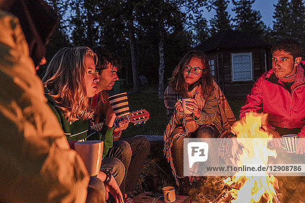 Group of friends sitting at a campfire,  talking and drinking tea