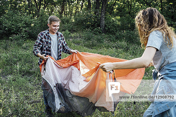 Young couple camping in nature  setting up tent