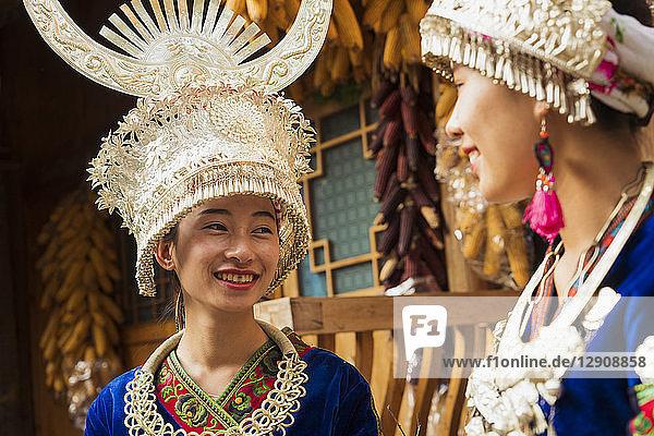 China  Guizhou  two smiling young Miao women wearing traditional dresses and headdresses