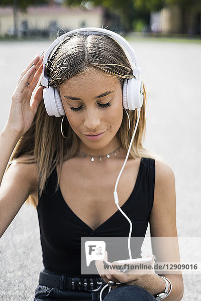 Relaxed teenage girl wearing headphones listening to music