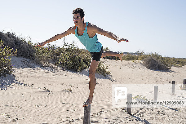 Spain  Canary Islands  Fuerteventura  young man exercising on the beach balancing on a pole