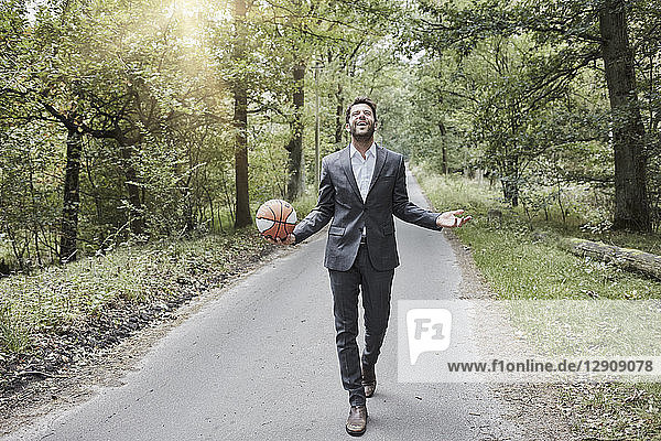 Happy businessman walking with basketball on rural road