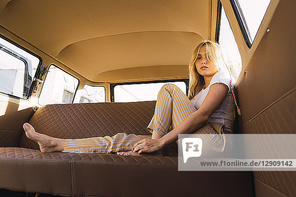 Portrait of young woman sitting in a van