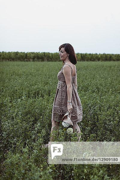 Woman wearing summer dress  walking in meadow  holding flowers