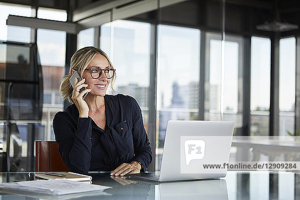 Businesswoman sitting in office  talking on the phone