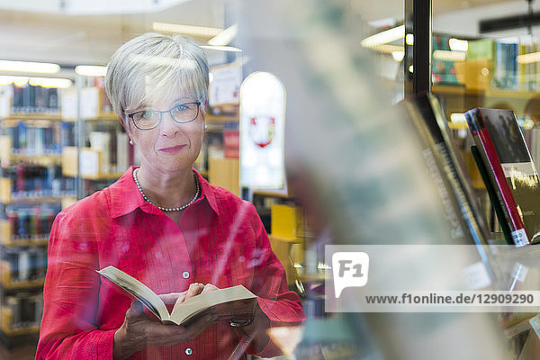 Portrait of senior woman behind glass pane in a city library