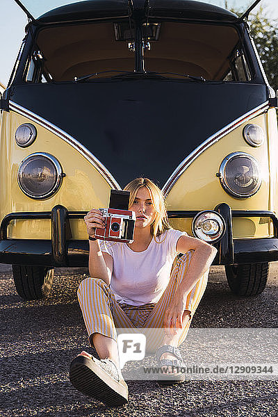 Young woman holding vintage camera sitting outside at a van