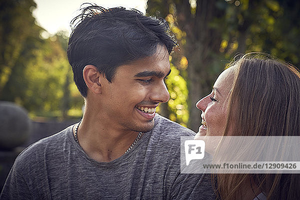Happy young couple flirting in a park in summer