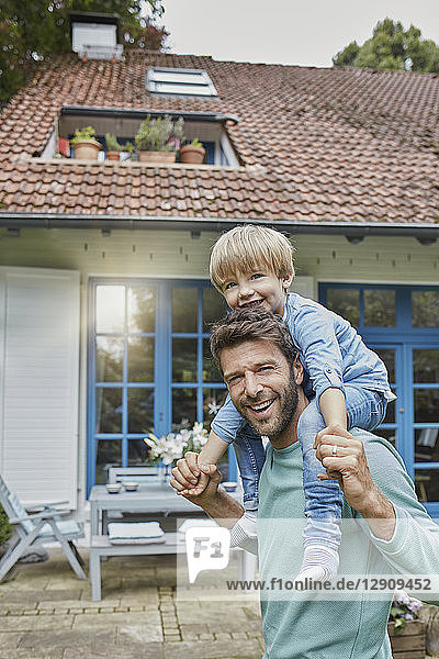 Portrait of happy father carrying son on shoulders in front of their home