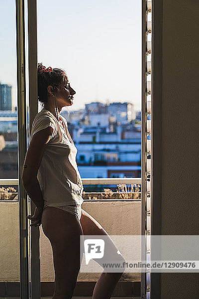Young woman in t-shirt and panties at home standing at the window