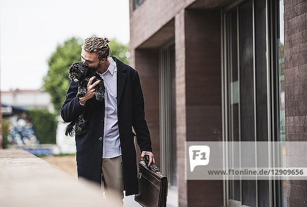 Young businessman cuddling dog outside office building