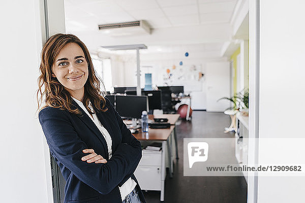 Confident businesswoman standing smiling in office