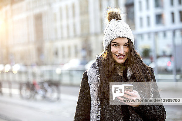 Portrait of smiling young woman with cell phone in winter