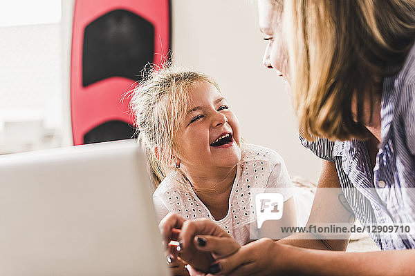 Mother and daughter having fun  using laptop