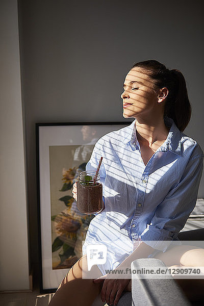 Young woman drinking smoothie at home